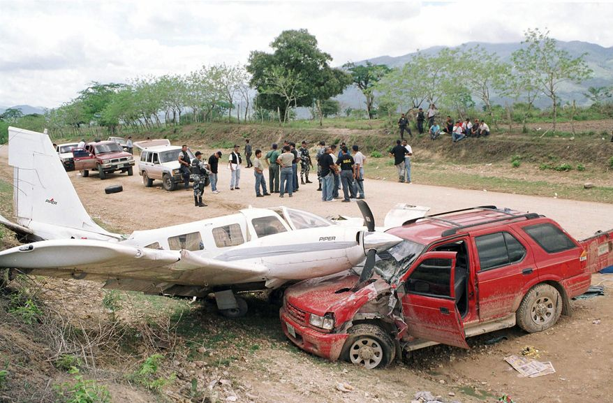 """An airplane lies crashed on the hood of a car that was used by police to prevent the plane from escaping after pilots unloaded drugs into several cars in San Esteban, Honduras, in 2003. """"Honduras is the No. 1 offload point for traffickers to take cocaine through Mexico to the U.S.,"""" said a U.S. law enforcement official. (Associated Press)"""