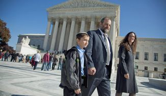 Ari Zivotofsky accompanies his son, Menachem, outside the Supreme Court in Washington on Monday. The Supreme Court seemed unlikely to rule in favor of the 9-year-old, who was born in Jerusalem and whose parents want his United States passport to list his place of birth as Israel. (Associated Press)