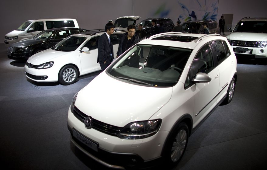 A salesman (center left) and a visitor (center right) check out a Volkswagen CrossGolf at an import car expo in Beijing on Tuesday, Nov. 1, 2011. (AP Photo/Alexander F. Yuan)