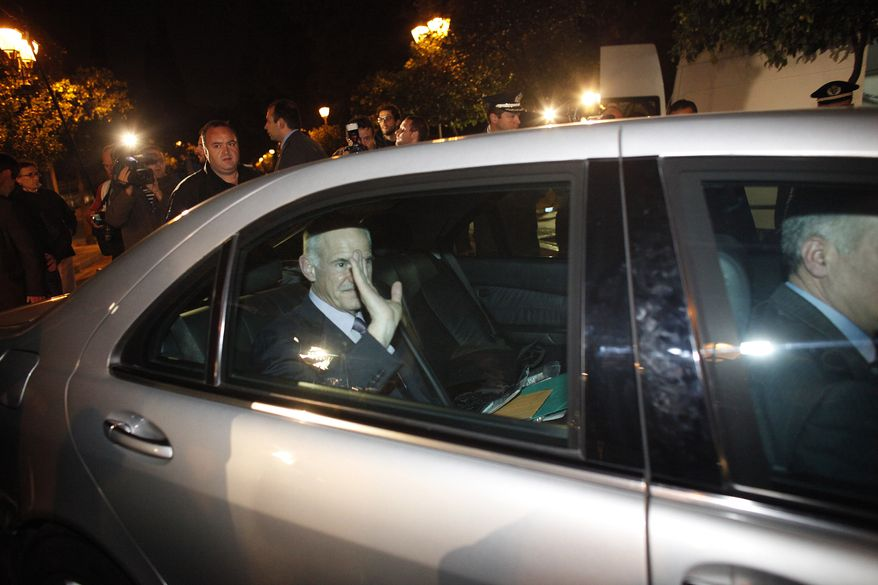 Greek Prime Minister George Papandreou waves to journalists as he leaves the Presidential Palace in Athens on Sunday, Nov. 6, 2011, after a meeting with Greek President Karolos Papoulias and opposition leader Antonis Samaras. (AP Photo/Kostas Tsironis)