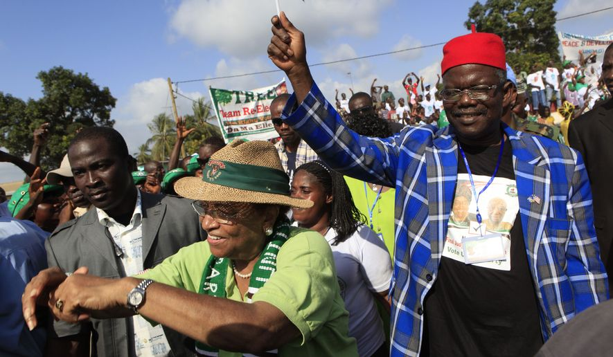 Liberian President Ellen Johnson Sirleaf (front), with Prince Johnson (right), arrives for a rally at the Stephen Tubman Estates in Monrovia, Liberia, on Sunday, Nov. 6, 2011, the last day of campaigning before Tuesday's runoff election. (AP Photo/Rebecca Blackwell)
