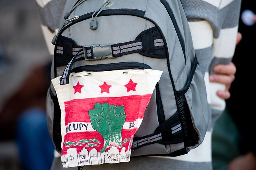 An Occupy DC protester wears a cloth sign on his backpack as a group of protesters converge on the front steps of the Metropolitan Police Headquarters at 300 Indiana Avenue, Monday, November 7, 2011. (Andrew Harnik / The Washington Times)