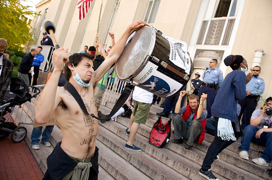 William G. Estrella, living in McPherson Square on K Street beats a drum as protesters, upset by multiple hit-and-run incidents last Friday during a protest of the American for Prosperity Conference outside the Washington Convention Center, converge on the front steps of the Metropolitan Police Headquarters at 300 Indiana Avenue, Monday, November 7, 2011. (Andrew Harnik / The Washington Times)