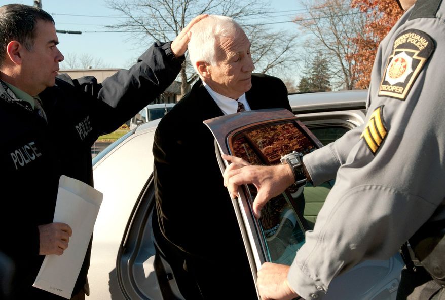 "Former Penn State football defensive coordinator Gerald ""Jerry"" Sandusky (center) is placed in a police car in Bellefonte, Pa., to be taken to the office of a Centre County Magisterial District judge on Saturday, Nov. 5, 2011.  (AP Photo/Pennsylvania Office of Attorney General, Commonwealth Media Services)"
