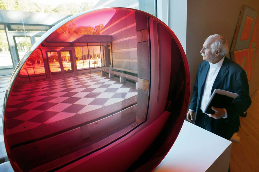 Architect Moshe Safdie gazes out a window next to a large, untitled magnifying disk sculpture at the Crystal Bridges Museum of American Art in Bentonville, Ark. The museum is scheduled to open Friday. (Associated Press)