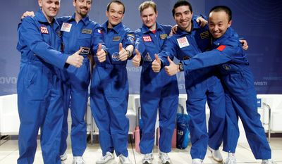 An international crew of researchers - from left, Alexey Sitev of Russia, Romain Charles of France, Suhrob Kamolov of Russia, Alexander Smoleevskiy of Russia, Diego Urbina of Italy/Colombia and Wang Yue of China - gives a thumbs-up after a 520-day simulation of a flight to Mars, in Moscow on Tuesday. (Associated Press)