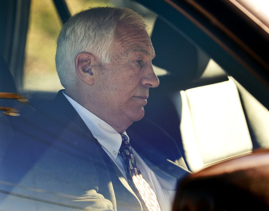 """Former Penn State football defensive coordinator Gerald """"Jerry"""" Sandusky sits in a car as he leaves the office of Centre County Magisterial District Judge Leslie A. Dutchcot on Saturday, Nov. 5, 2011, in State College, Pa. Sandusky is charged with sexually abusing eight young men. (AP Photo/The Patriot-News, Andy Colwell)"""