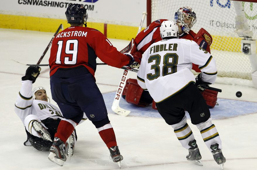 Dallas Stars left wing Eric Nystrom, left, falls as he scores a goal on Washington Capitals goalie Michal Neuvirth, rear, as Capitals center Nicklas Backstrom and Stars center Vernon Fiddler watch during the third period of an NHL game in Washington, Tuesday, Nov. 8, 2011. The Stars won 5-2. (AP Photo/Ann Heisenfelt)