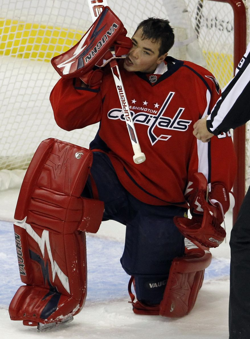 Washington Capitals goalie Michal Neuvirth rubs his face after losing his helmet from a hard hit with the puck during the first period of an NHL game against the Dallas Stars in Washington, Tuesday, Nov. 8, 2011. (AP Photo/Ann Heisenfelt)