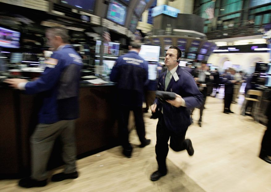 Trader Michael Zicchinolfi runs across the New York Stock Exchange floor on Wednesday. The Dow Jones industrial average fell nearly 400 points as the European debt crisis sent American stocks into a tailspin. (Associated Press)