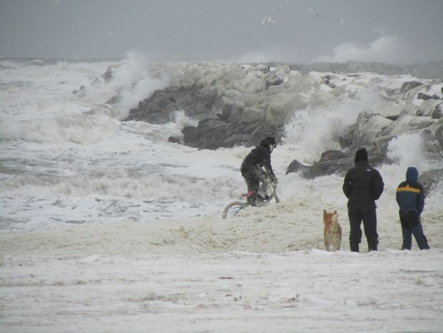 Kids in Nome, Alaska, play in sea foam near the town's harbor late on Tuesday, Nov. 8, 2011, as a big Bering Sea storm starts kicking up waves. (AP Photo/Peggy Fagerstrom)
