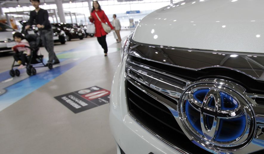 Visitors walk by vehicles on display at a Toyota Motor Corp. showroom in Tokyo on Tuesday, Nov. 8, 2011. (AP Photo/Koji Sasahara)