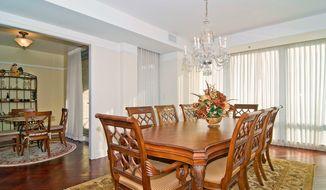 The formal dining room has a wall of windows, a tray ceiling and herringbone-patterned hardwood flooring.