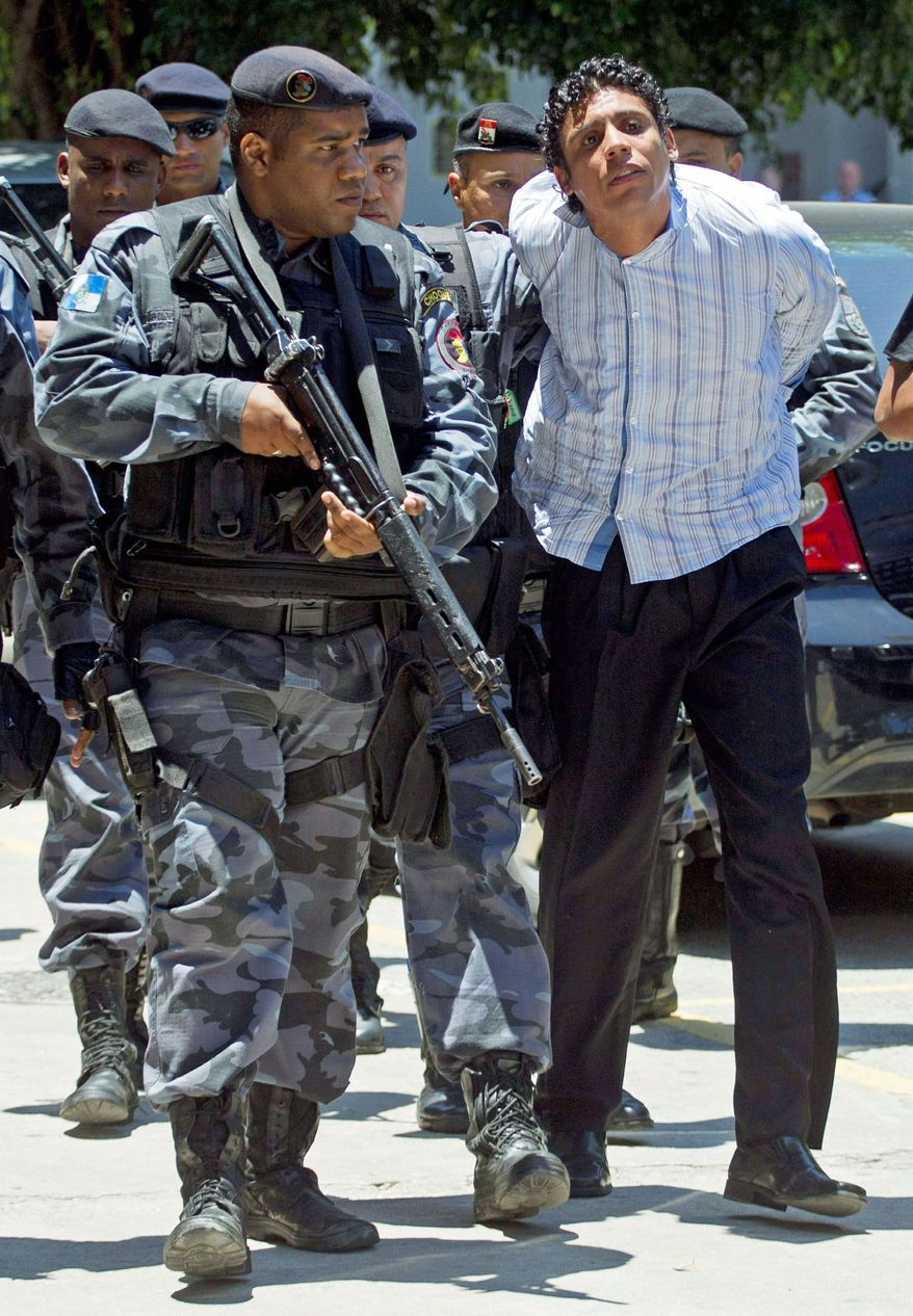 Antonio Bonfim Lopes (right) is escorted Thursday by police to federal police headquarters in Rio de Janeiro. He is believed to be the drug-trafficking kingpin of the city. His capture is considered a blow to the drug gang that controls one of Latin America's biggest slums and the main drug distribution point in Rio. (Associated Press)