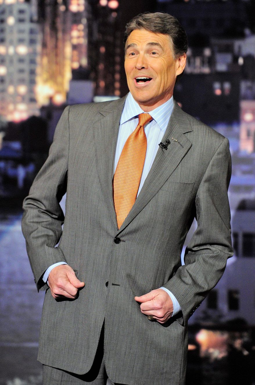 """Texas Gov. Rick Perry reads the """"Top Ten"""" list on David Letterman's Thursday show. He was a late addition to the show after stumbling in Wednesday's GOP debate. (CBS via Associated Press)"""