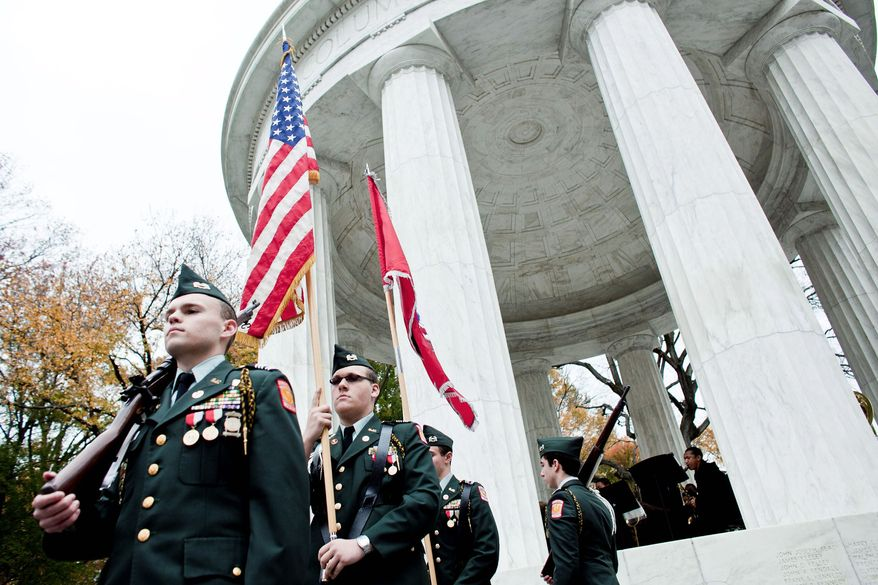 HONOR GUARD: Alexander Hubichi (from left), Matthew Cranford, Thomas Shedlick, and Matthew Shipley, Army JROTC cadets at St. John's College High School, carry the colors Thursday at the District of Columbia War Memorial. (T.J. Kirkpatrick/The Washington Times)