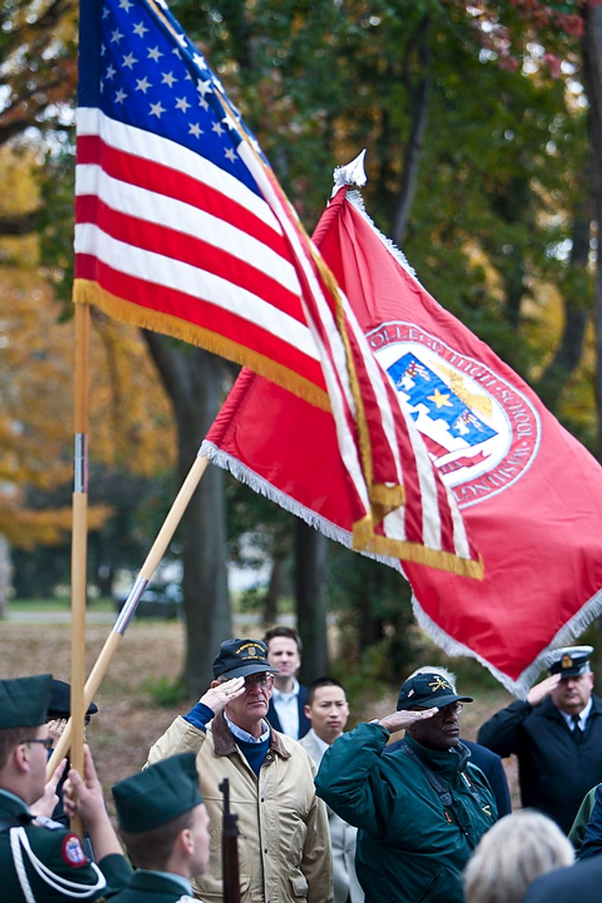 Tom Rogan, from left, of Fayston, Vt., and Dr. Tom Brannon, of Nashville, Tenn., both Vietnam veterans from the 4th Cavalry Regiment 1st Infantry Division, salute the colors as the National Anthem is sung during a rededication ceremony following renovations of the District of Columbia WWI Memorial in Washington, D.C. on Nov. 10, 2011.