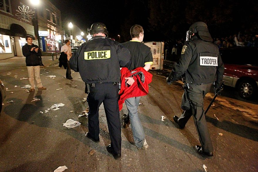 A student is taken into police custody on Thursday, Nov. 10, 2011, following a gathering of Penn State students and others off campus after the firing of football coach Joe Paterno and university President Graham Spanier on Wednesday, Nov. 9, 2011, in State College, Pa. (AP Photo/Matt Rourke)