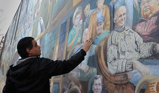 ** FILE ** Michael Pilato paints over the image of Jerry Sandusky, a former defensive coordinator at Penn State, on a mural on College Avenue in State College, Pa., on Wednesday, Nov. 9, 2011. (AP Photo/Pittsburgh Post-Gazette, Lake Fong)