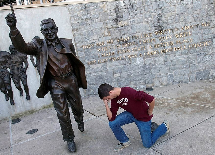 "Penn State sophomore Andrew Barney kneels like Denver Broncos football player Tim Tebow, who prays during football games, beside a statue of Penn State football coach Joe Paterno  on the school's campus in State College, Pa., on Tuesday, Nov. 8, 2011. According to Barney, he was ""tebowing"" in a show of support for Paterno. (AP Photo/York Daily Record, Jason Plotkin)"