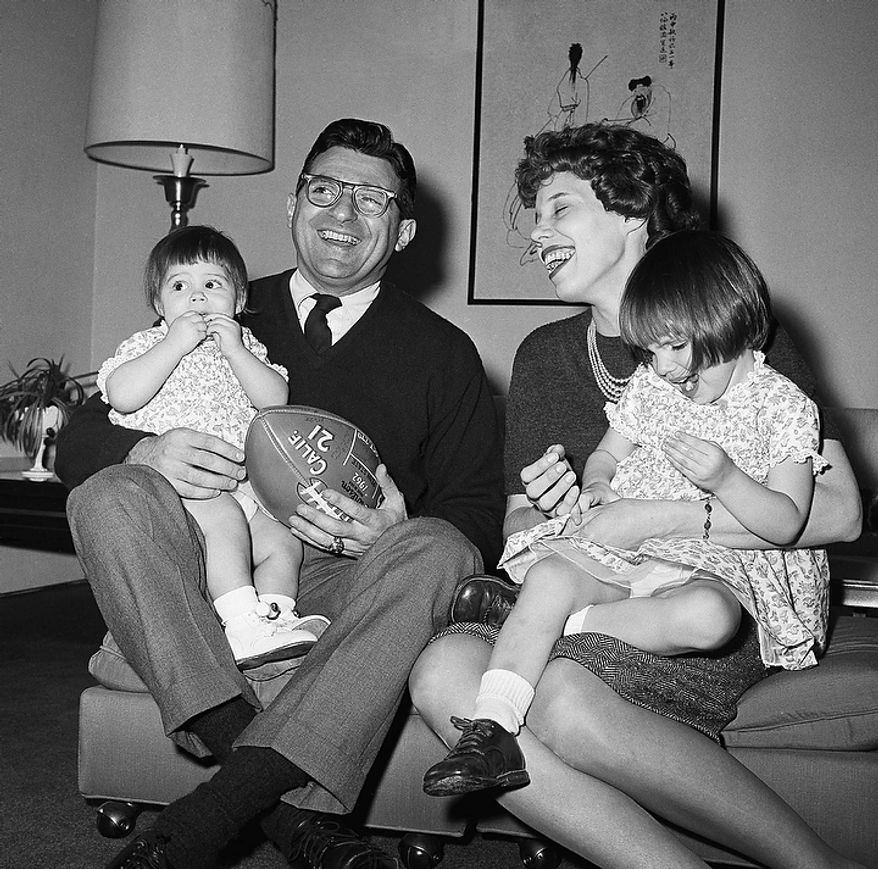 In this Feb. 16, 1966 file photo, new Penn State head football coach Joe Paterno poses with his one-year-old daughter Mary Kathryn on his lap and his wife Suzanne, with two-year-old daughter Diana Lynne, at their home in University Park, Pa. Paterno say he plans to retire at the end of the season, his long and illustrious career brought down because he failed to do all he could about an allegation of child sex abuse against a former assistant. (AP Photo/Paul Vathis, File)
