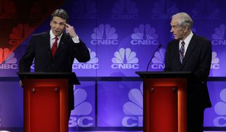 Republican presidential candidate Texas Gov. Rick Perry points to his head as he speaks during a Republican Presidential Debate at Oakland University in Auburn Hills, Mich., Wednesday, Nov. 9, 2011. At right is Rep. Ron Paul, R-Texas. (AP Photo/Paul Sancya)