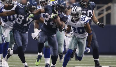 Seattle Seahawks Ben Obomanu (87) looks on as running back Marshawn Lynch (24) fights for extra yardage as Dallas Cowboys cornerback Alan Ball (20) gives chase during an NFL football game Sunday, Nov. 6, 2011, in Arlington, Texas. (AP Photo/Jim Cowsert)