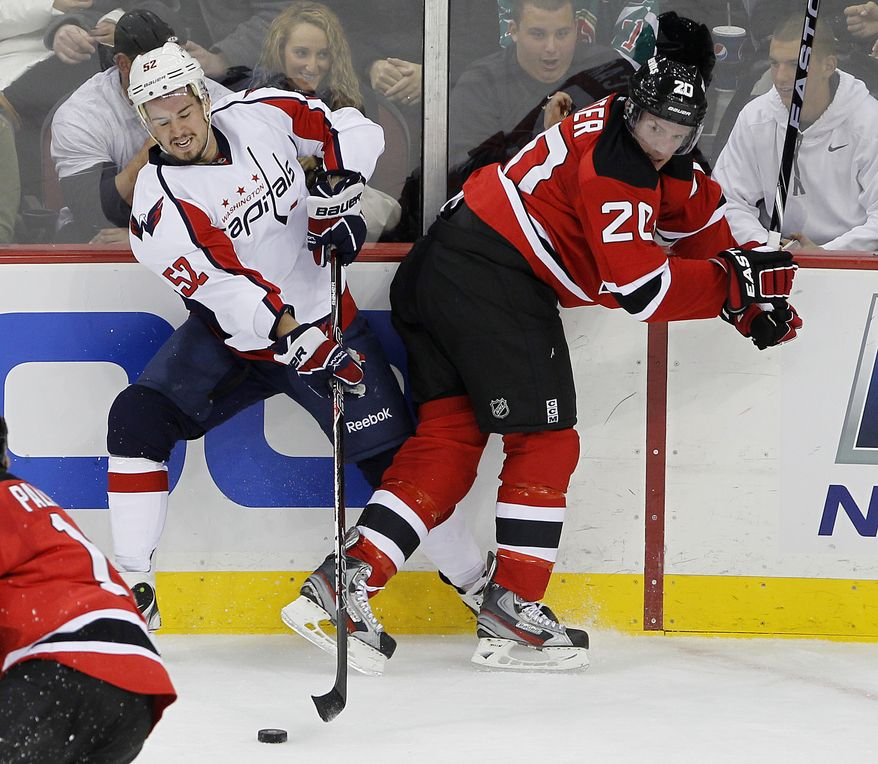 Mike Green (left) of the Washington Capitals controls the puck despite being hit into the boards by the New Jersey Devils' Ryan Carter during the first period on Friday, Nov. 11, 2011, in Newark, N.J. (AP Photo/Rich Schultz)