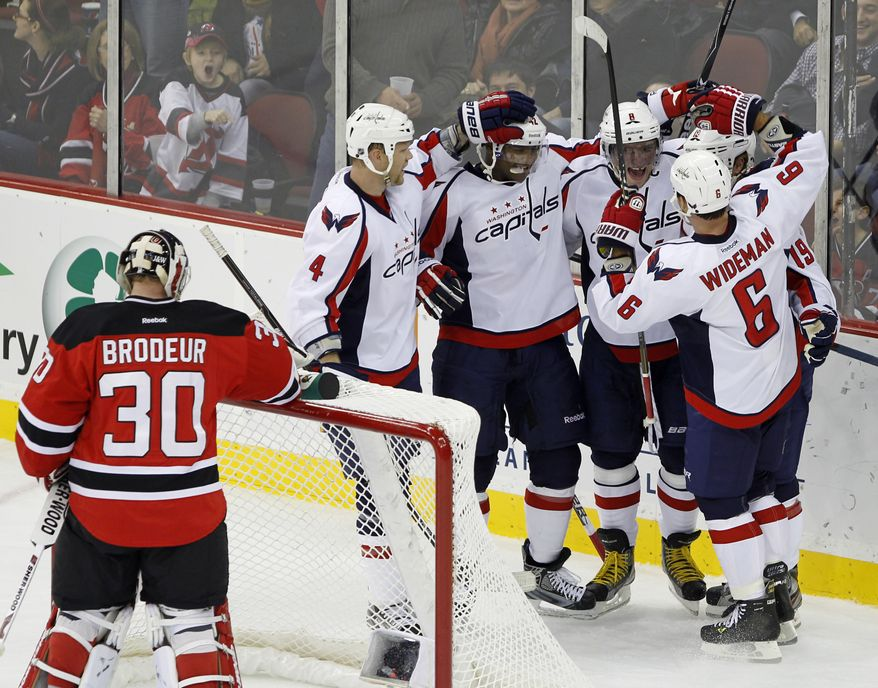 Washington Capitals' Alex Ovechkin is congratulated by teammates John Erskine, Joel Ward (42), Nicklas Backstrom and Dennis Wideman after scoring a goal against New Jersey Devils goalie Martin Brodeur during the second period in Newark, N.J., Friday, Nov. 11, 2011. The Caps won 3-1 (AP Photo/Rich Schultz)