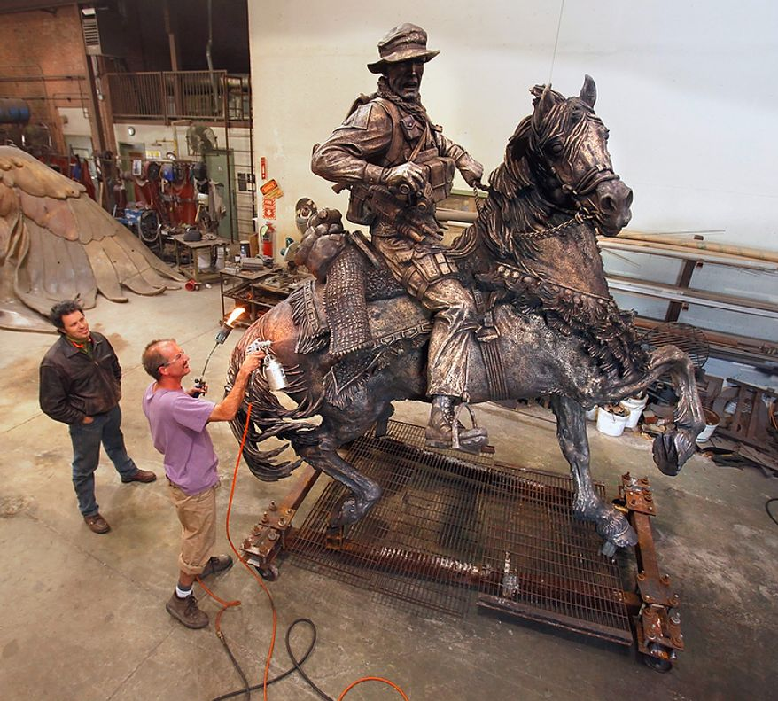 In a Friday, Nov. 4, 2011, photo, Douwe Blumberg, left, watches as Todd Jenkins puts a patina on Blumberg's statue honoring U.S. Special Forces serving in Afghanistan, in Norman, Okla. It was expected to be unveiled on Veteran's Day near the World Trade Center site in New York. (AP Photo/The Oklahoman, Steve Sisney)