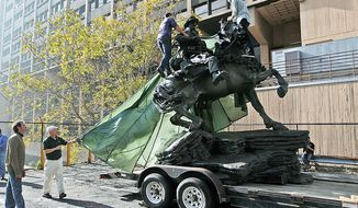 "Artist Douwe Blumberg, left, watches as a tarp is removed from his ""De Opresso Liber"" statue, Thursday, Nov. 10, 2011, in New York. The 16-foot bronze statue honoring the U.S. special operations response to 9/11 was expected to be unveiled Nov. 11, 2011, by Vice President Joe Biden and Dr. Jill Biden. (AP Photo/Mary Altaffer)"