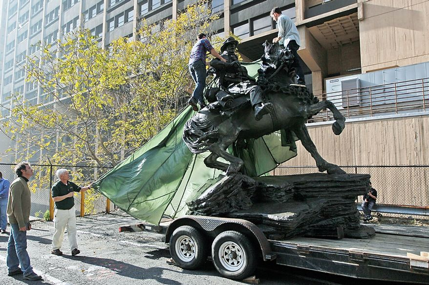 """Artist Douwe Blumberg, left, watches as a tarp is removed from his """"De Opresso Liber"""" statue, Thursday, Nov. 10, 2011, in New York. The 16-foot bronze statue honoring the U.S. special operations response to 9/11 was expected to be unveiled Nov. 11, 2011, by Vice President Joe Biden and Dr. Jill Biden. (AP Photo/Mary Altaffer)"""