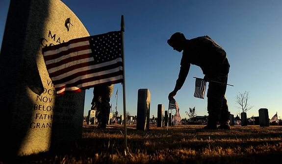 Staff Sgt. Tim Slusser puts a flag at one of the headstones at the Texas State Veterans Cemetary in Abilene, Texas, on Thursday, Nov. 10, 2011, in preparation for Veteran's Day on Friday. (AP Photo/Abilene Reporter-News, Tommy Metthe)
