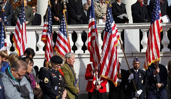 Guest bow their heads for a moment of silence during a Veteranís Day ceremony where President Barack Obama spoke, Friday, Nov. 11, 2011,  at Arlington National Cemetery in Arlington, Va.(AP Photo/Pablo Martinez Monsivais)