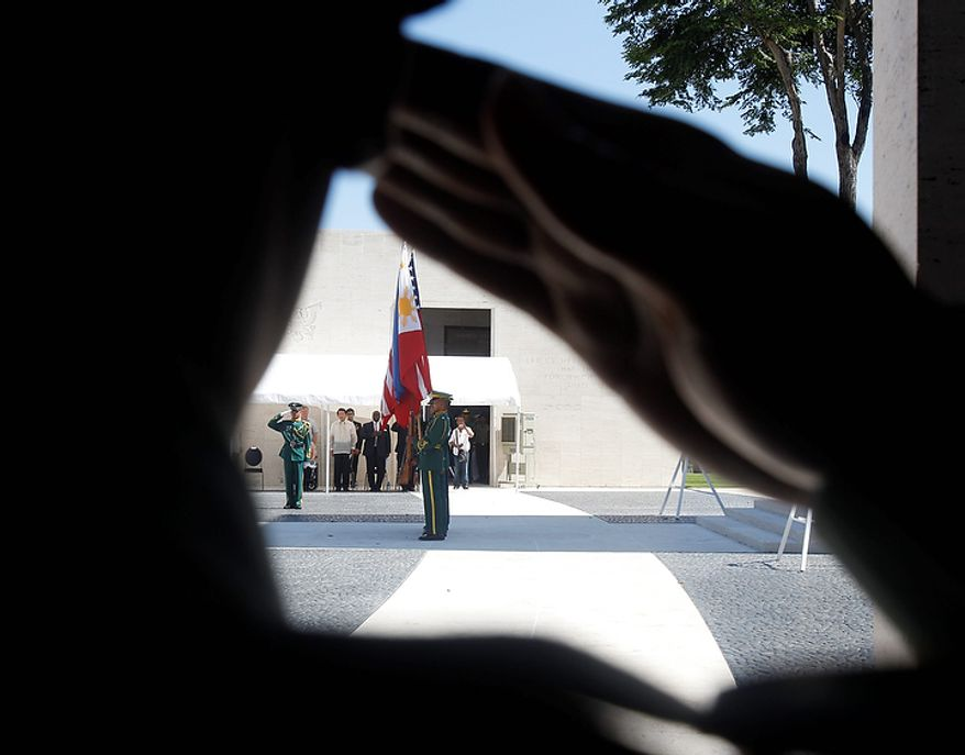 A U.S. Marine salutes the colors during a wreath-laying ceremony at the American Cemetery and Memorial at suburban Taguig city, east of Manila, Philippines, as they pay tribute to U.S. veterans and their families on Veterans Day Friday, Nov. 11, 2011. The Manila American Cemetery and Memorial contains the remains of WWII Americans who died in the Pacific, China, India, and Burma along with Philippine Scouts who served with the U.S. forces. (AP Photo/Bullit Marquez)