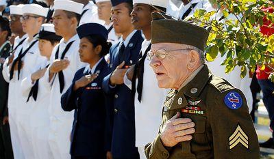 Korean War veteran James Gerard, right, wearing his original uniform, salutes during a Veteran's Day observance at Fort Sam Houston National Cemetery, Friday, Nov. 11, 2011, in San Antonio. (AP Photo/Eric Gay)