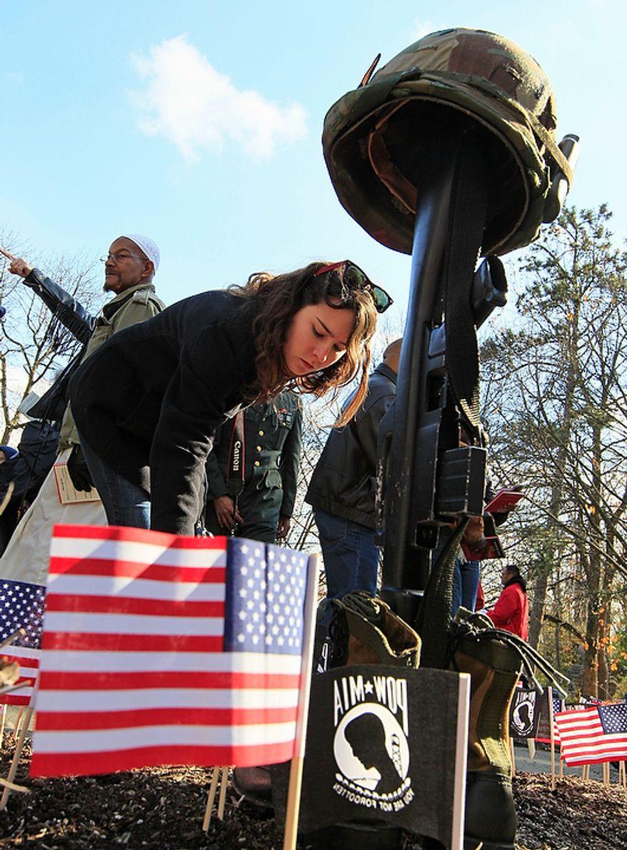 Taylor Norton places a U.S. flag in front of the Vietnam Veteran's memorial following a Veteran's Day ceremony, Friday, Nov. 11, 2011, in Eden Park in Cincinnati. (AP Photo/Al Behrman)