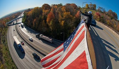 Standing atop Crest Drive in Chattanooga, Tenn., Vietnam-era veterans Robert Bunch, Ron Tatum and Ron Harvey wave to motorists along I-24   in celebration of Veterans Day on Friday, Nov. 11, 2011.  (AP Photo/Chattanooga Times Free Press, Tracey Trumbull)