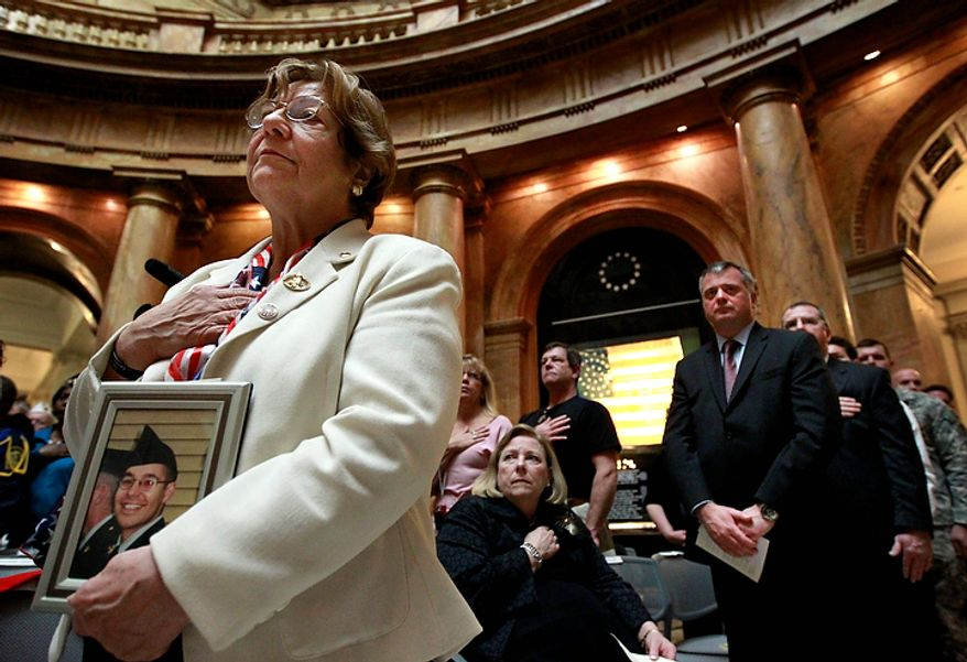 Gold Star Mother Santina Raymond, of Lawrence, Mass., front left, holds a photograph of her fallen son U.S. Army Sgt. Pierre Raymond, during Veterans Day ceremonies at the Statehouse, in Boston, Friday, Nov. 11, 2011. Sgt. Raymond died Sept. 20, 2005 from injuries sustained during combat in Iraq. (AP Photo/Steven Senne)