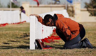 Juanita Moreno visits the grave site of her brother during a Veteran's Day observance at Fort Sam Houston National Cemetery, Friday, Nov. 11, 2011, in San Antonio. (AP Photo/Eric Gay)