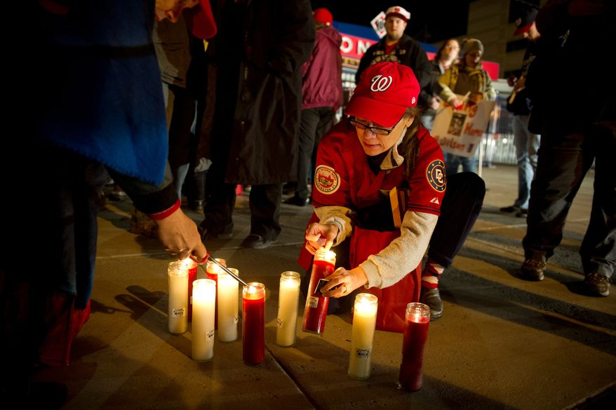 Michi Szpatura of Arlington, Va, lights candles for other to hold during a candlelight vigil for Nationals' rookie catcher Wilson Ramos at Nationals Park in Washington, DC, Friday, November 11, 2011. Ramos was kidnapped by armed gunmen in front of his family home in Venezuela on Wednesday night. (Rod Lamkey Jr. / The Washington Times)