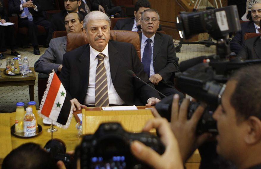 Yussef al-Ahmad, Syria's ambassador to the Arab League, is surrounded by cameramen during the Arab League emergency session on Syria at the Arab League headquarters in Cairo, Egypt, Saturday, Nov.12, 2011. The Arab League has voted to suspend Syria from all meetings until it implements a plan to end bloodshed. (AP Photo/Amr Nabil)