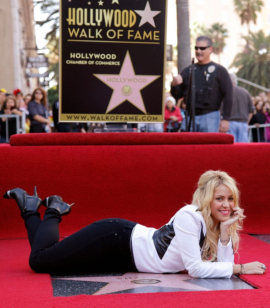 Colombian singer Shakira relaxes next to her star on the Hollywood Walk of Fame in Los Angeles. Now 34, she released her first album at age 14. (Associated Press)
