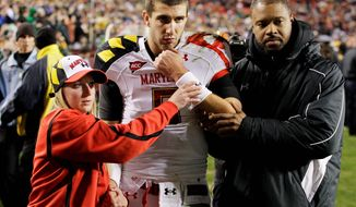 Maryland quarterback Danny O'Brien is helped off the field after suffering a broken bone in his left arm on the next-to-last-play Saturday against Notre Dame. O'Brien was 14-for-21 and a touchdown in the Terrapins 45-21 loss at FedEx Field. (Associated Press)