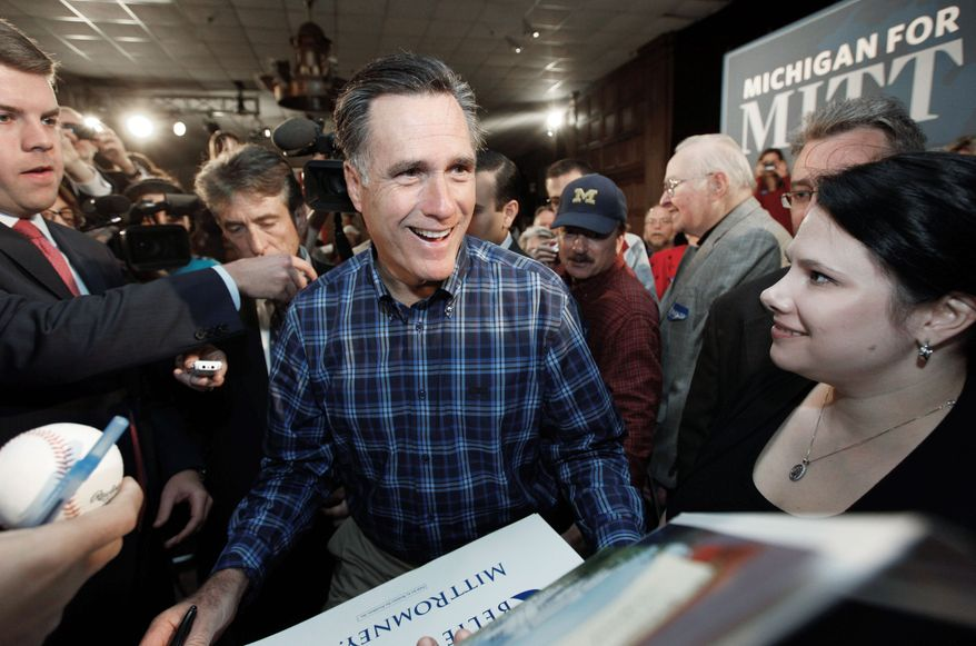 Republican presidential hopeful Mitt Romney greets supporters in Troy, Mich., on Thursday. The night before, in a GOP candidates debate, the former Massachusetts governor sought to defuse criticism of his changing his views on the issues. (Associated Press)