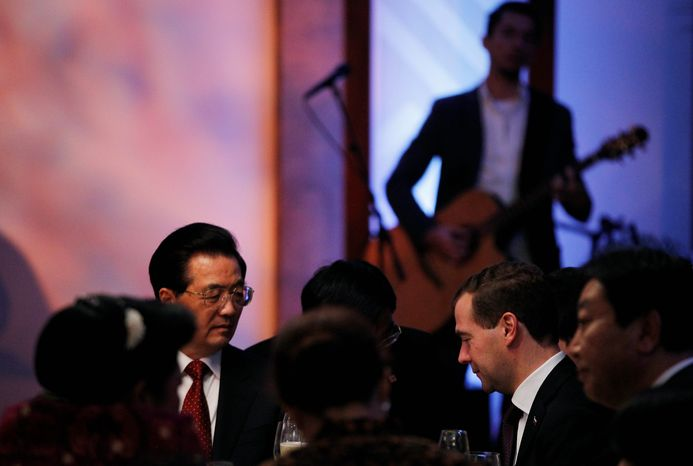 """Guitarist Makana (background) wore an """"Occupy With Aloha"""" T-shirt at the dinner of the Asia-Pacific Economic Cooperation summit Saturday night and sang his new song, """"We Are the Many."""" (Associated Press)"""