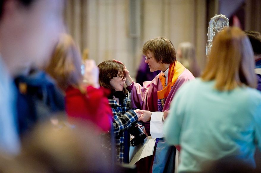 Bishop Mariann Edgar Budde, the first woman to serve as bishop of the Washington Episcopal Diocese, speaks with a member of the congregation following a service. (Andrew Harnik/The Washington Times)