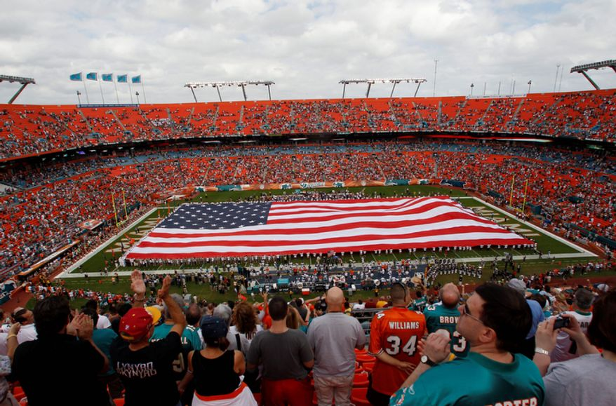 A large U.S. flag is displayed in honor of Veterans Day before an NFL football game between the Miami Dolphins and the Washington Redskins, Sunday, Nov. 13, 2011, in Miami. (AP Photo/Hans Deryk)