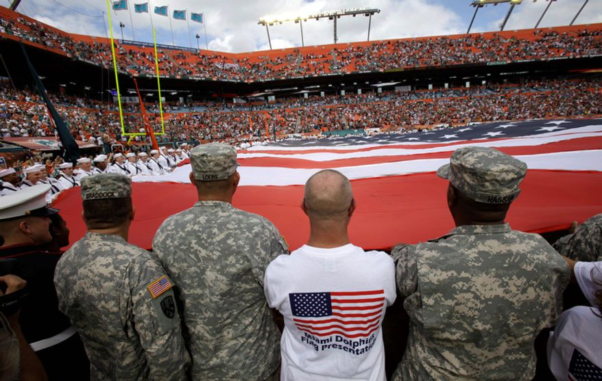 A giant United States flag is held on the field by military personnel in honor of Veterans Day before of an NFL football game between the Miami Dolphins and the Washington Redskins, Sunday, Nov. 13, 2011, in Miami. (AP Photo/Lynne Sladky)