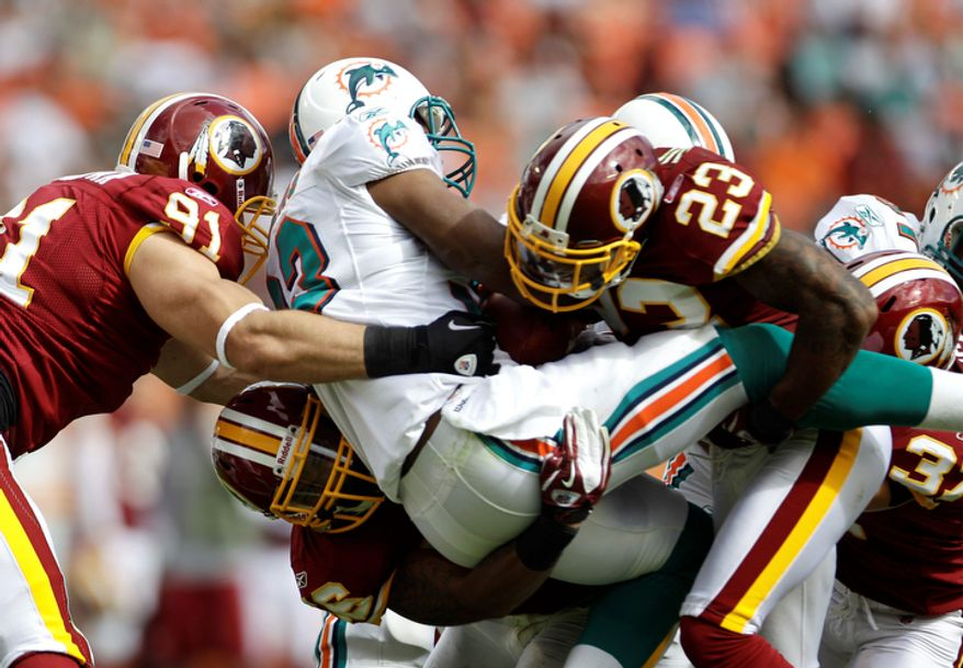 Miami Dolphins running back Daniel Thomas, center, is tackled by Washington Redskins outside linebacker Ryan Kerrigan (91), cornerback DeAngelo Hall (23) and other defenders during the first quarter. (AP Photo/J Pat Carter)